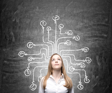Young businesswoman looking up, labyrinth with each line ending in a bulb painted on the blackboard behind her. Front view. Concept of making choice.